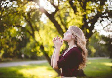 femme priant sous un arbre pendant la journée