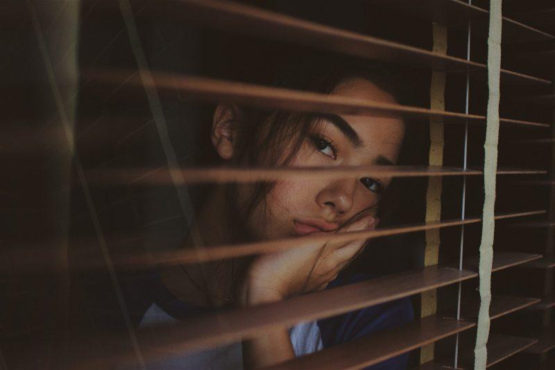une femme appuyée contre une fenêtre