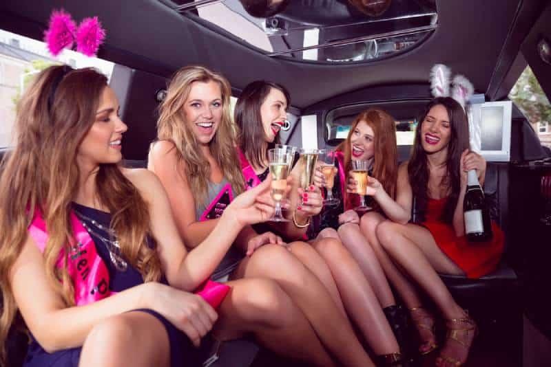 Des amis heureux qui boivent du champagne en limousine lors d'une soirée