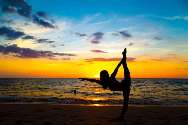 Des sportives en bonne santé font du yoga et de la méditation au coucher du soleil sur la plage