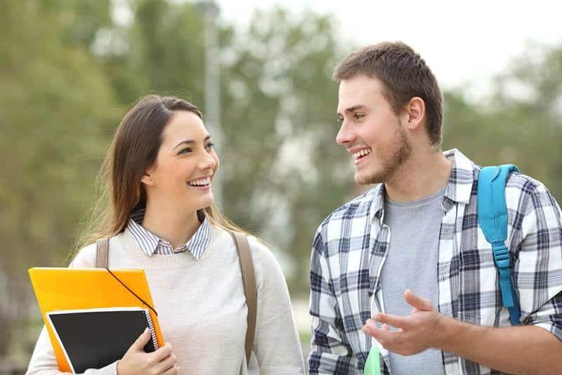 Deux étudiants souriants discutent à l'extérieur