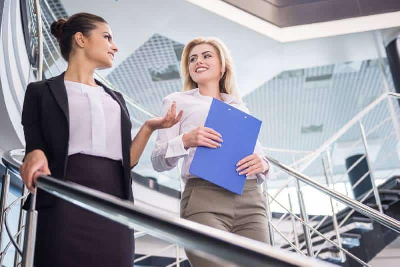 Deux femmes d'affaires séduisantes descendent les escaliers et discutent.