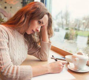 Une jeune femme triste écrit une lettre avec un cœur brisé et se sentant désespérée