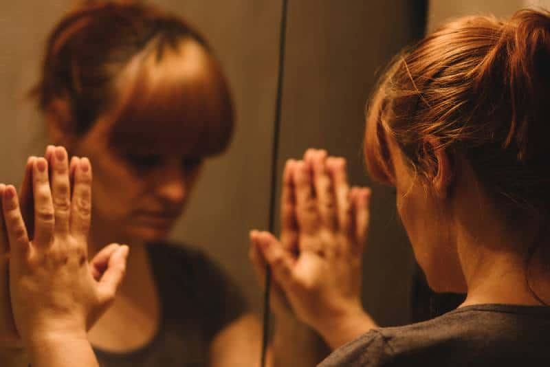 Femme triste et solitaire regardant son reflet dans le miroir