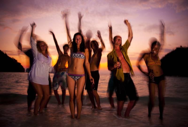 Grand groupe de jeunes gens dansant sur une plage paradisiaque