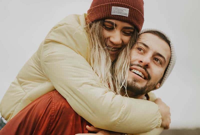 Gros plan homme portant une femme souriante avec un chapeau