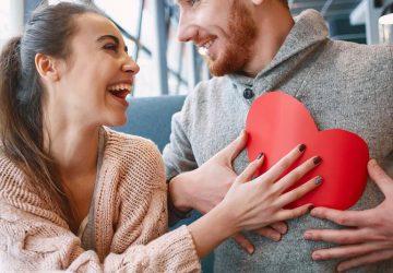 Une femme souriante donne à son homme une forme de coeur en papier