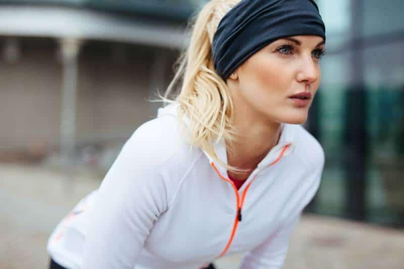 Jeune femme se penchant dans un équipement sportif