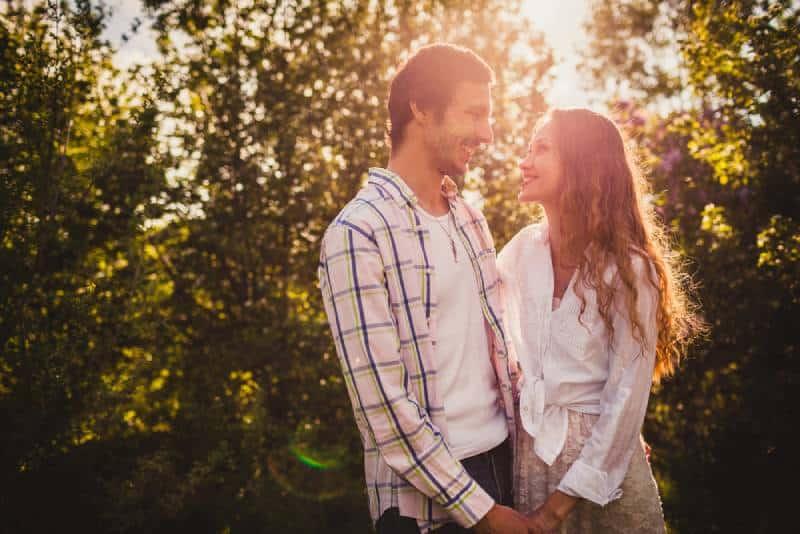 joli couple se tenant devant une feuille et se regardant