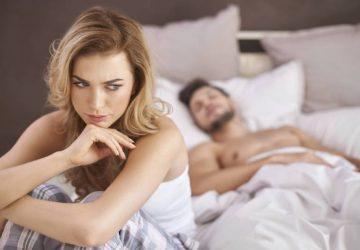 femme réfléchie assise sur le lit alors que l'homme est couché