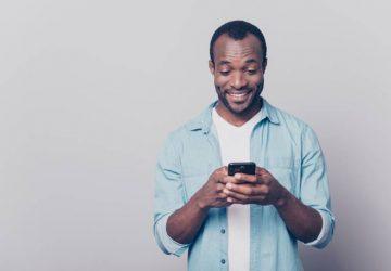 Un type curieux portant un jean décontracté et une chemise en denim envoie et reçoit des messages