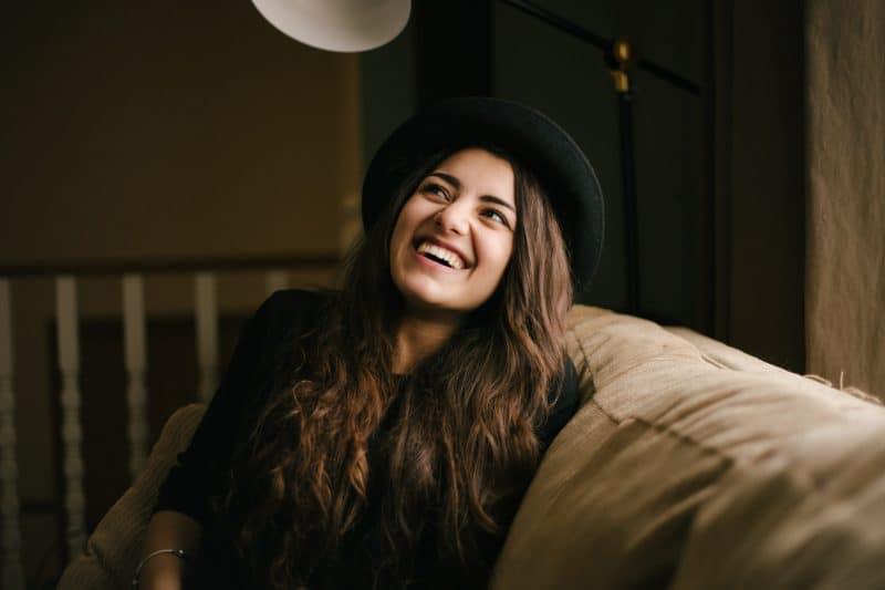 une femme brune avec un chapeau sur la tête