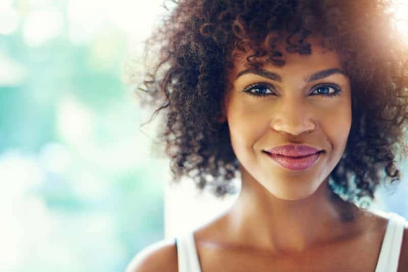 Portrait d'une jeune femme noire souriante avec une torche de soleil