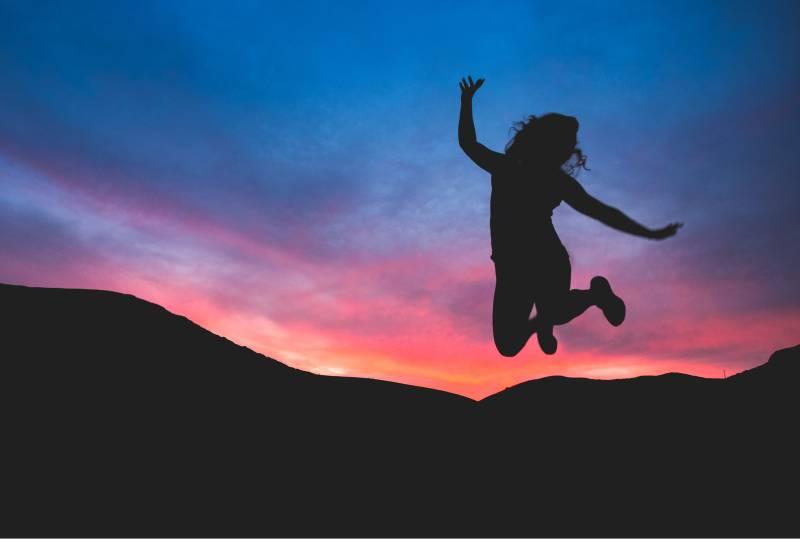 Silhouette de la personne qui saute à l'aube