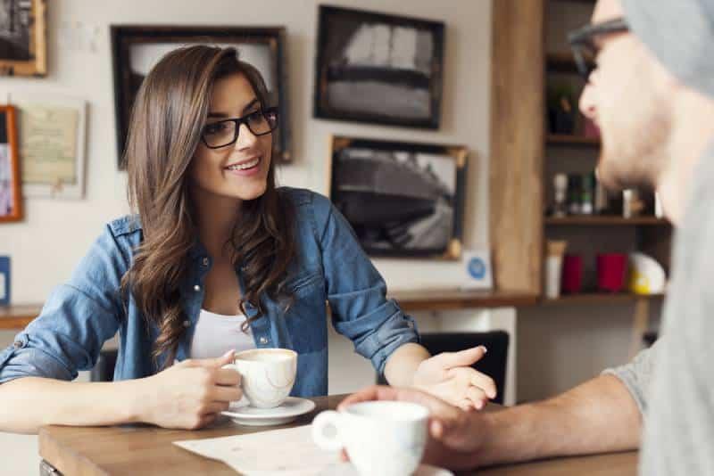Un couple de hipsters parle dans un café