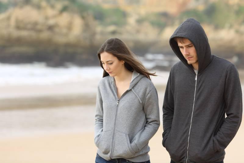 Un couple malheureux se promène sur la plage