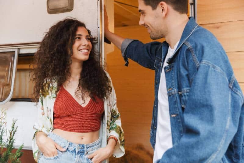 Un couple souriant parle en se tenant près de la maison