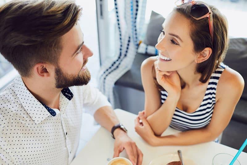 Un couple souriant qui se regarde en s'asseyant sur la table