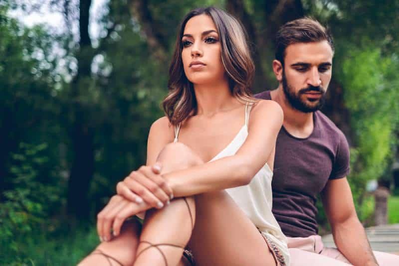 Un couple triste assis dans le parc et pensant
