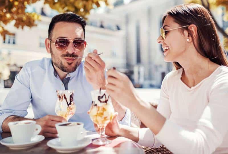 Un homme et une femme heureux en mangeant une glace au café