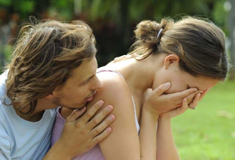 Un homme réconforte sa petite amie en pleurs à l'extérieur