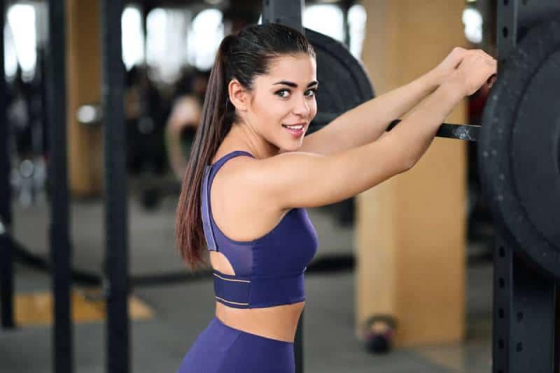 Une belle jeune femme brune et athlétique en tenue de sport à la salle de sport