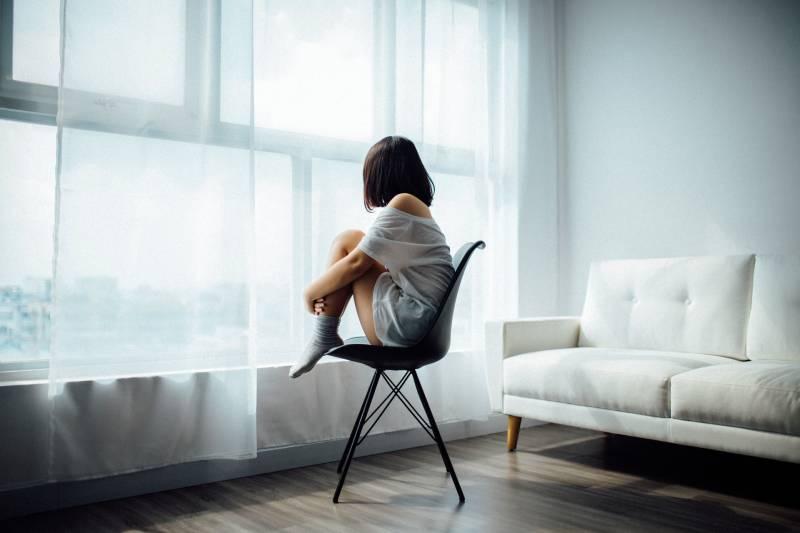 Une femme inquiète qui regarde par la fenêtre
