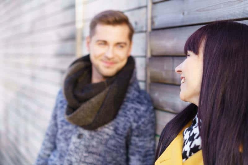 Une femme mignonne se tient dehors et regarde l'homme avec un sourire chaleureux