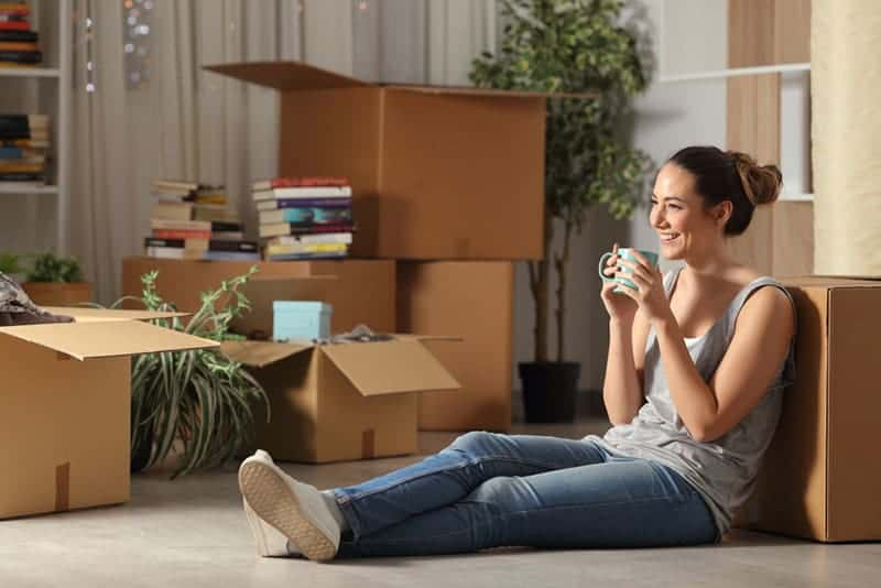 Une femme souriante assise par terre à la maison