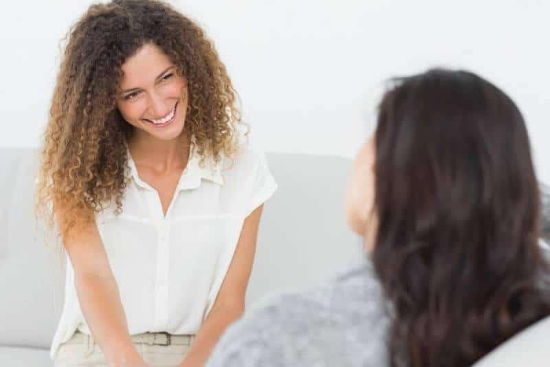 Une femme souriante tient la main d'une autre femme