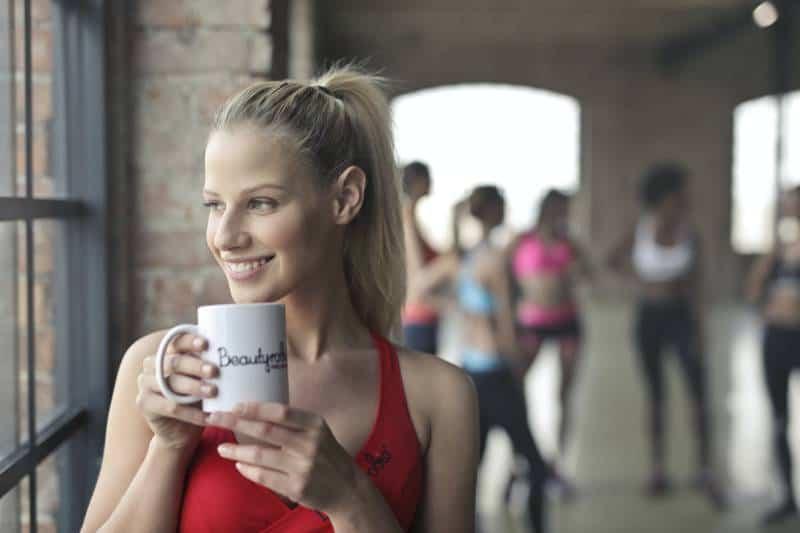 Une femme tient des tasses en céramique blanche près d'une fenêtre en verre tout en souriant