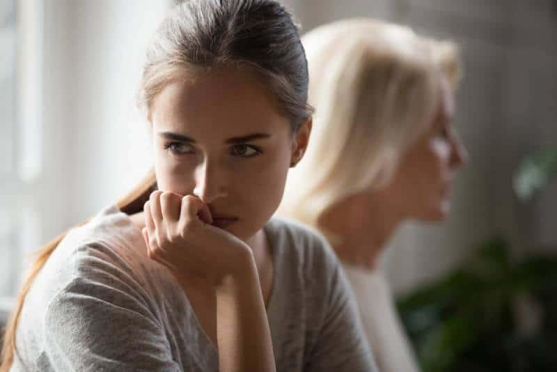 Une fille adulte et une mère âgée offensée s'assoient dos à dos pour éviter de parler après la bagarre