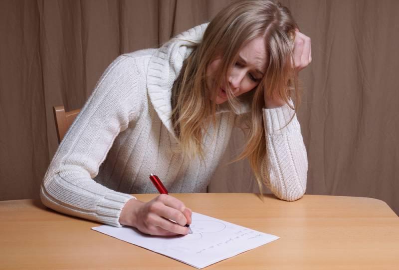 Une jeune femme en mal d'amour écrit une lettre avec le cœur brisé