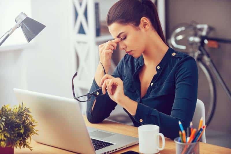 Une jeune femme frustrée garde les yeux fermés alors qu'elle est assise sur son lieu de travail dans le bureau