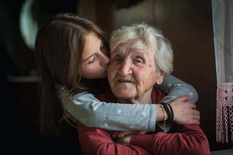 Une petite fille embrasse sa grand-mère.