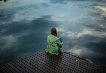 une femme imaginaire est assise à côté de la jetée, le dos tourné