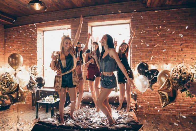 Vue en taille réelle d'un joli groupe de femmes séduisantes et royales s'amusant à danser sur le lit