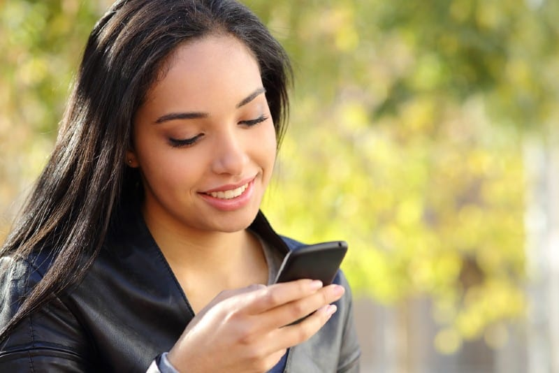 belle femme écrivant sur son téléphone