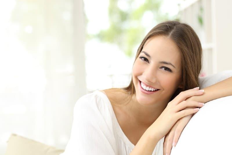 belle femme souriante assise sur un canapé