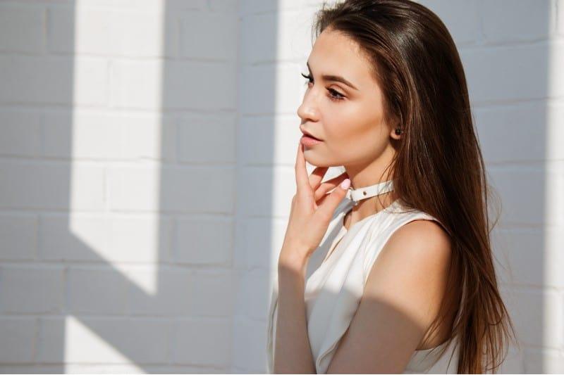 une belle jeune femme vêtue d'une robe blanche pensant