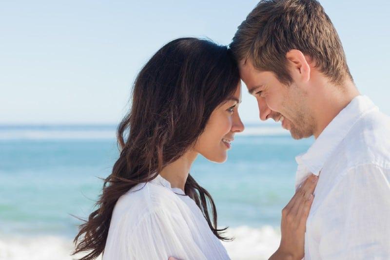 Couple attrayant embrassant sur la plage par une journée ensoleillée