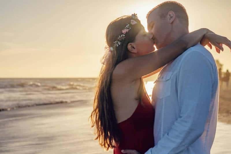 couple de plage affectueux s'embrassant à contre-jour