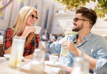un homme et une femme à une table à l'extérieur pendant la journée