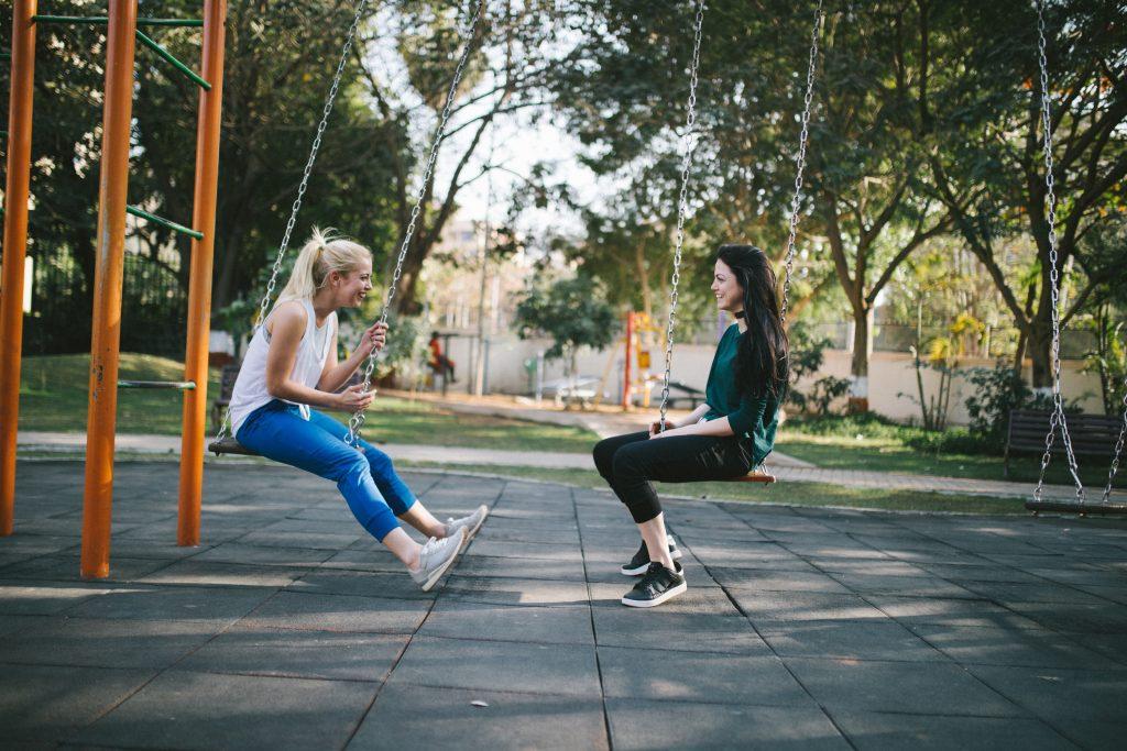 deux femmes s'assoient sur des balançoires et rient