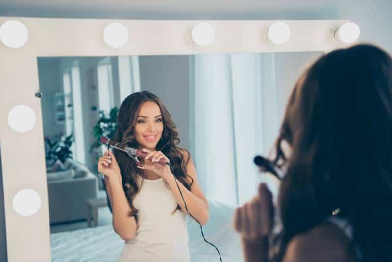 douce dame attirante faisant des boucles tout en se regardant dans un miroir
