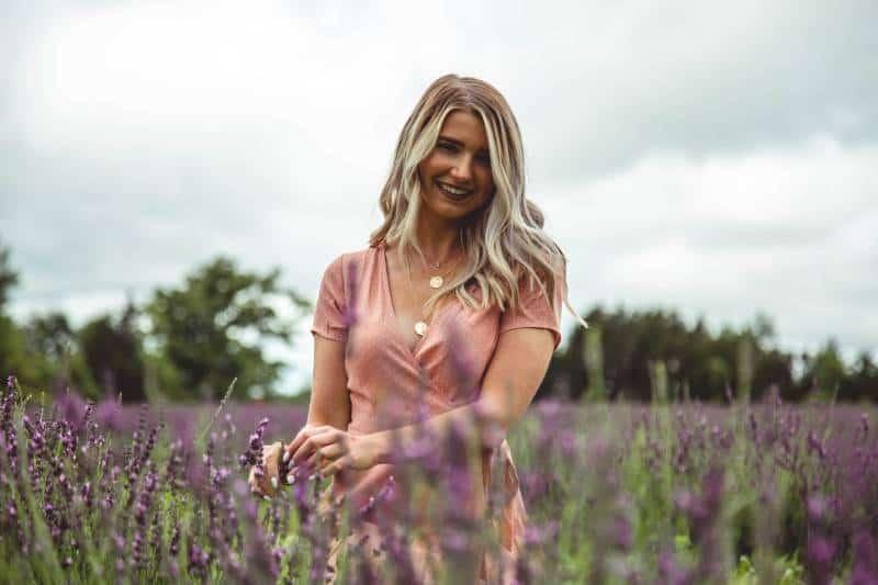 femme blonde au milieu d'un champ de fleurs violettes