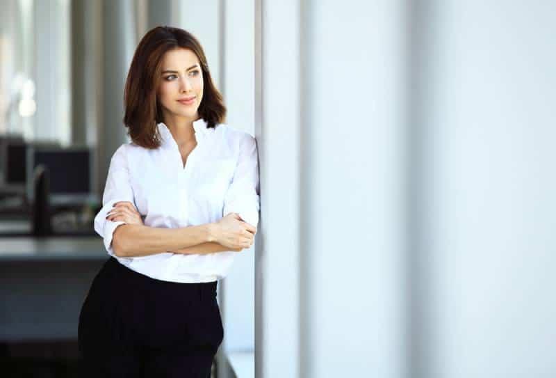 femme d'affaires en chemise blanche aux bras croisés, debout à côté de la fenêtre