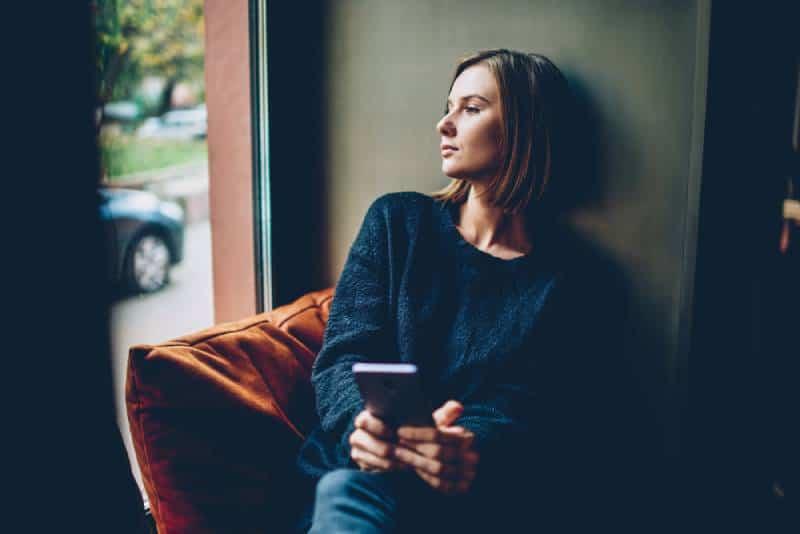 femme réfléchie tenant son téléphone et assise à côté de la fenêtre