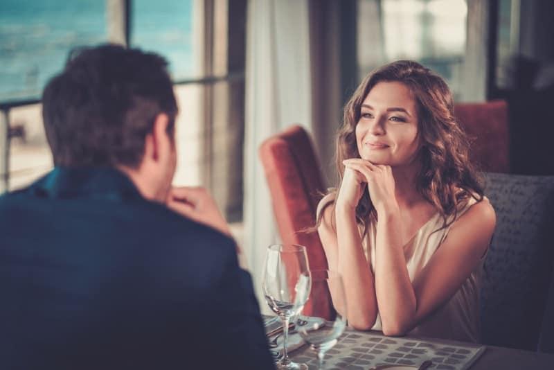 une femme souriante regardant un homme assis à une table devant elle