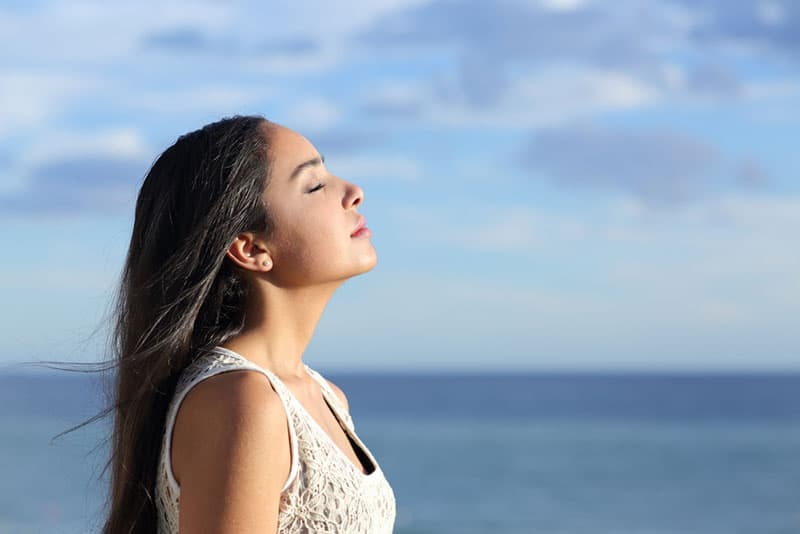 femme respirant profondément par la mer